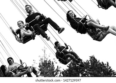 PARIS, FRANCE - May 26, 2019: People (kids with parents) have fun riding Chain Carousel at Jardin d'Acclimatation, popular children's amusement park located in Bois de Boulogne. Black white photo.