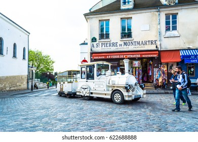 Paris, France - May 27, 2015: Old tourist locomotive train at the Montmartre in Paris. One of the most famous and visited tourist districts of Paris.