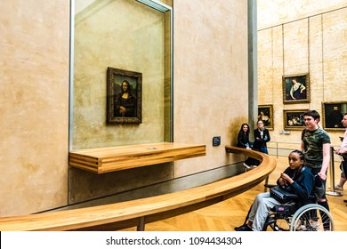 PARIS, FRANCE - MAY 27, 2016: Many people appreciate paintings in the Louvre Museum in Paris, France. The Louvre is the world's largest museum and a historic monument in Paris, France.