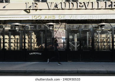 """Paris, France - May 27, 2021: a woman is jogging and passes in front of the brewery """"le vaudeville"""" closed because of the restictions due to the coronavirus crisis"""