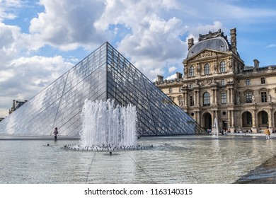 PARIS, FRANCE - MAY 29, 2018: View of pyramid and fountain at main courtyard (Cour Napoleon) of Louvre Museum. Louvre Museum is one of the largest and most visited museums worldwide.