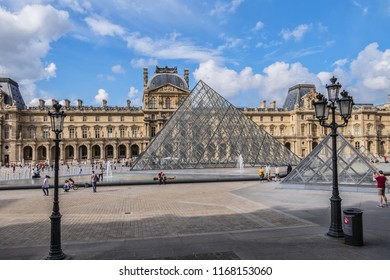 PARIS, FRANCE - MAY 29, 2018: View fragments of Louvre buildings and pyramid in main courtyard (Cour Napoleon) of Louvre Museum. Louvre Museum is one of largest and most visited museums worldwide.