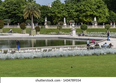 PARIS, FRANCE - MAY 29, 2019: Tourists and Parisians relaxing in Luxembourg Garden (Jardin du Luxembourg). Jardin du Luxembourg - second largest Public Park in Paris.