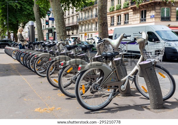 PARIS, FRANCE - May 29: Street view with unknown woman paying for renting a bicycle on May 29, 2015, Paris, France