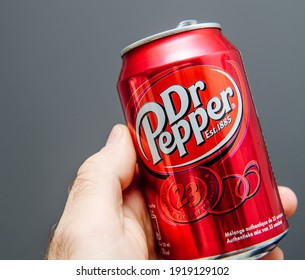 Paris, France - May 3, 2020: POV male hand holding aluminum can of Dr Pepper manufactured by Dr Pepper Snapple Group soft sweet drinks - isolated against gray background