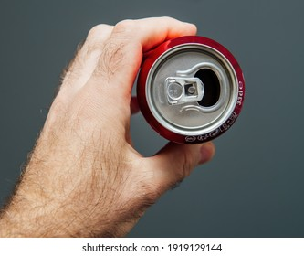 Paris, France - May 3, 2020: POV male hand holding top of aluminum can of Dr Pepper manufactured by Dr Pepper Snapple Group soft sweet drinks - isolated against gray background - recycling concept