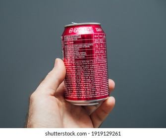 Paris, France - May 3, 2020: POV male hand holding top of aluminum can of Dr Pepper manufactured by Dr Pepper Snapple Group soft sweet drinks - isolated against gray background - reading reference
