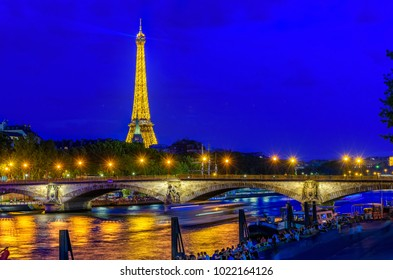 Paris, France - May 30, 2017: Night view of Eiffel tower, Pont des Invalides and Seine river in Paris, France. Architecture and landmarks of Paris. Postcard of Paris