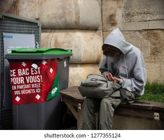 PARIS, FRANCE - MAY 30, 2018: Student using mobile phone in park near trash can with massage: This trash bin (BAC meaning trash bin in French, but it is also abbreviation of Baccalaureate) for you!