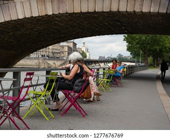 PARIS, FRANCE - MAY 30, 2018: Mature women using smart phones while relaxing sitting at cafe tables at Parisian embankment promenade with a view of Conciergerie. Urban lifestyle scene.