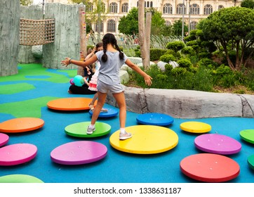 PARIS, FRANCE - MAY 30, 2018: Girls jumping over round trampolines at playground at reconstructed Les Halles square park. New kids attraction near Saint-Eustache church.