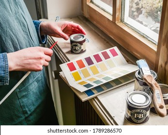 Paris, France - May 30, 2020: Side view of woman looking at the colour chart with sample pot of Farrow and ball luxury British paint preparing to paint the wall and window frame