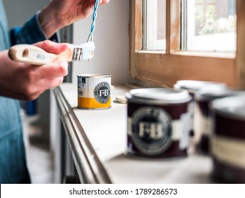 Paris, France - May 30, 2020: Side view of woman testing paint sample pot of Farrow and ball luxury British paint preparing to paint the wall and window frame