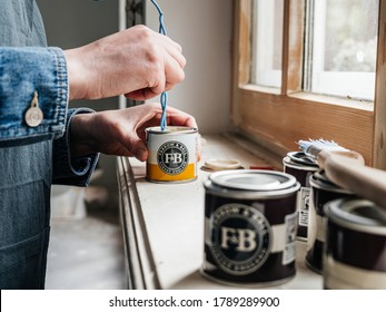 Paris, France - May 30, 2020: Close-up side view of woman mixing paint sample pot of Farrow and ball luxury British paint preparing to paint the wall and window frame