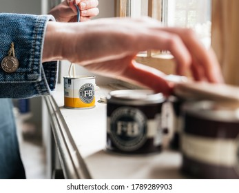 Paris, France - May 30, 2020: Close-up side view of woman testing paint sample pot of Farrow and ball luxury British paint preparing to paint the wall and window frame