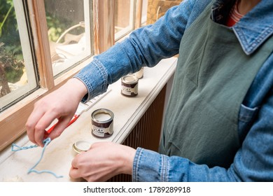Paris, France - May 30, 2020: Overhead view of young woman testing paint sample pot of Farrow and ball luxury British paint preparing to paint the wall and window frame