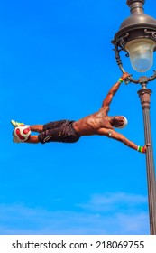 Paris, France - May 4, 2014: Incredible Football Freestyle Iya Traore hanging on Lamp Post and juggling a Soccer Ball in front of Sacre Coeur church.
