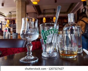 PARIS, FRANCE - MAY 4, 2018: Wide closeup of a glass with the Perrier luxury mineral water logo and ice next to a glass of scotch whisky at a cafe. Travel and drinks.