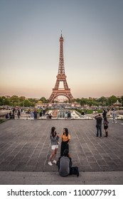 Paris, France - May 6, 2018: Tourists relaxing at Palais de Chaillot with  view on Eiffel Tower and Champ de Mars in Paris, France at sunset