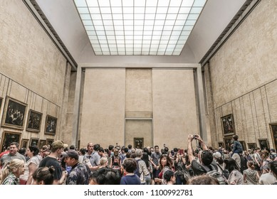 Paris, France - May 7, 2018: Crowd of the unidentified people take pictures of the Mona Lisa in Louvre, portrait painting by Leonardo da Vinci in Paris, France