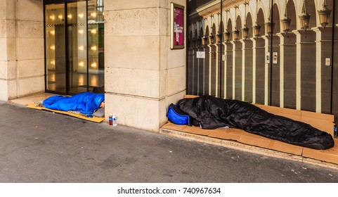 PARIS, FRANCE - MAY 8, 2017: The homeless clochard sleeps right on the street near Louvre of antique dealers. Paris, France