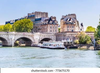 PARIS, FRANCE - MAY 9, 2017: The Vedettes du Pont Neuf tour boat on the Seine River near a bridge. Equestrian statue of Henri IV. Paris, France