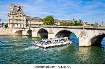 PARIS, FRANCE - MAY 9, 2017:  A tourist boat and tourists near Flora Pavilion ot the Louvre and Pont Royal. Paris. France