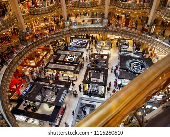 PARIS, FRANCE - MAY 9, 2018: Wide angle view of the central atrium and beautiful floors of Galeries Lafayette, with multiple brand name booths and logos. Shopping and luxury lifestyle editorial.