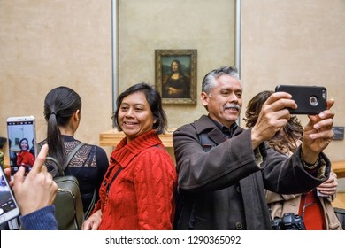 PARIS, FRANCE - Nov 08, 2017: Visitors do selfie and take photo of Leonardo Da Vinci's Mona Lisa at the Louvre Museumn. Mona Lisa or La Gioconda is one of the most valuable paintings in the world