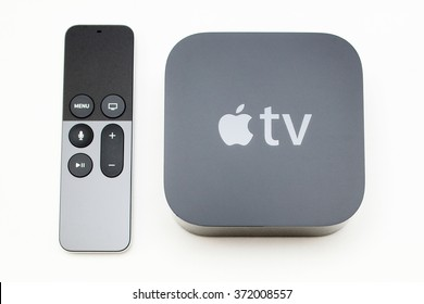 PARIS, FRANCE - NOV 10, 2015: New Apple TV 4k media streaming  player microconsole by Apple Computers next to the new touch remote swipe-to-select with integrated Siri and motion sensor on white