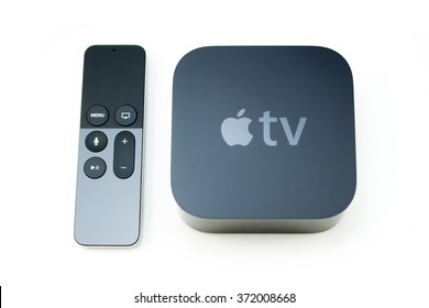 PARIS, FRANCE - NOV 10, 2015: New Apple TV media streaming  player microconsole by Apple Computers next to the new touch remote swipe-to-select with integrated Siri and motion sensor on white