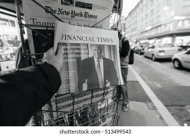 PARIS, FRANCE - NOV 10, 2016: Man buying Financial Times newspaper with headline title at press kiosk about the US President Elections - Donald Trump is the 45th President of United States of America