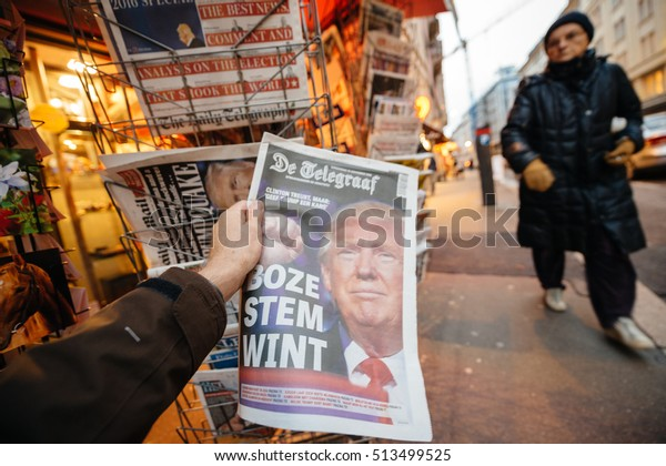 PARIS, FRANCE - NOV 10, 2016: Man buying Dutch newspaper with De Telegraaf headline title press kiosk about the US President Elections - Donald Trump is the 45th President of United States of America