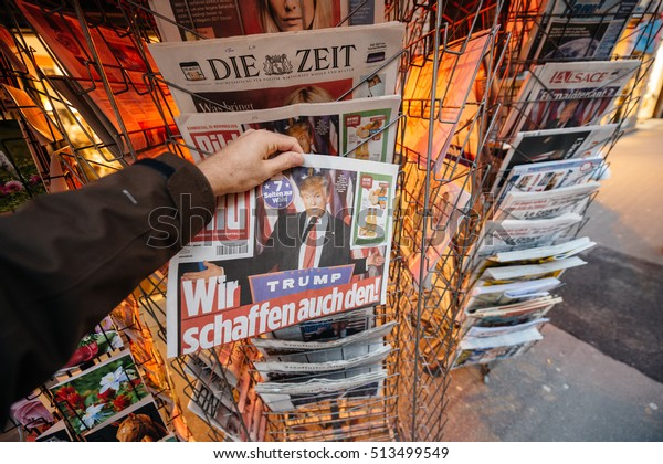 PARIS, FRANCE - NOV 10, 2016: Man buying newspaper with shocking headline title at press kiosk about the US President Elections - Donald Trump is the 45th President of United States of America