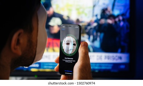 Paris, France - Nov 10. 2017: Face Obstructed message on display of new Apple iPhone XS Pro with Face ID virtual facial recognition function with anonymous hacker data monitor in the background