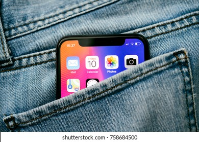 PARIS, FRANCE - NOV 10, 2017: New Apple iPhone X smartphone telephone mobile in pocket of fashion denim jeans pants trousers with home screen apps