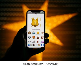 PARIS, FRANCE - NOV 10 2017: Cat 3d Animoji emoji generated by Face ID facial recognition system with different face emotion close-up the new Apple iPhone X 10 Display - yellow star bokeh background