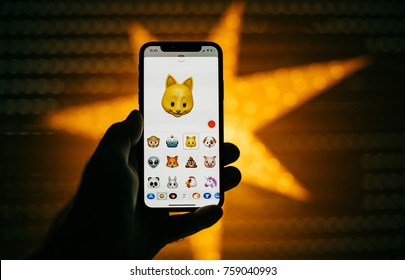 PARIS, FRANCE - NOV 10 2017: Cat 3d Animoji emoji generated Face ID facial recognition system with different face emotion close-up of the new Apple iPhone X 10 Display - yellow star bokeh background