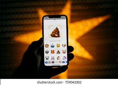 PARIS, FRANCE - NOV 10 2017: poop 3d Animoji emoji generated Face ID facial recognition system with different face emotion close-up of the new Apple iPhone X 10 Display - yellow star bokeh background