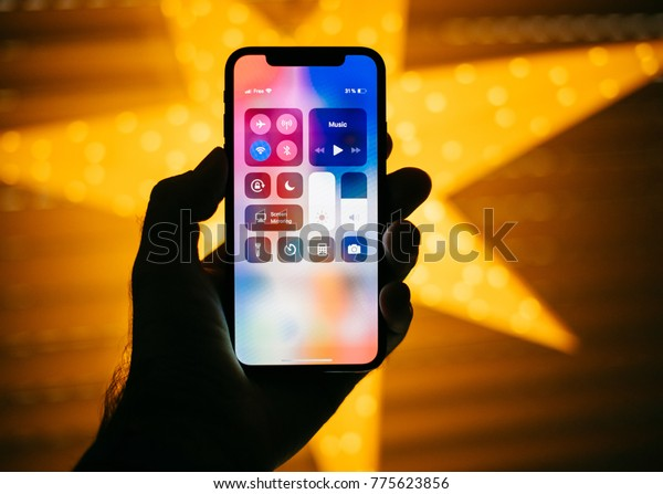 PARIS, FRANCE - NOV 10, 2017: Man holding the new Apple iPhone X 10 Display with yellow star bokeh background featuring Control Center buttons
