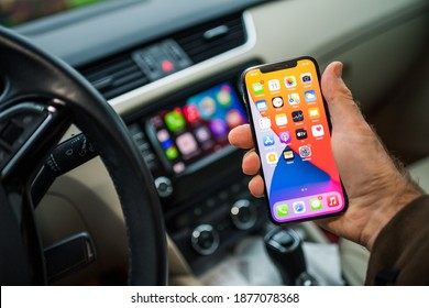 Paris, France - Nov 11, 2020: POV male driver holding new iPhone 12 Pro smartphone with infotainment car computer system running Apple Computers CarPlay from iOS in background