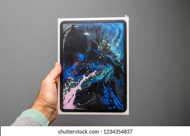 PARIS, FRANCE - NOV 14, 2018: Man holding POV the latest iPad Pro by Apple Computers tablet retail box against gray background