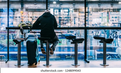 Paris, France - Nov 15, 2018: One man sits next to his luggage at a cafe overlooking passengers and trains below at Paris's Gare du Nord station
