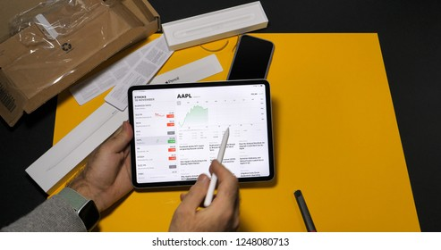 PARIS, FRANCE - NOV 16, 2018: Man using latest iPad Pro smart tablet device and Apple Pencil 2 manufactured by Apple Computers in modern office environment yellow table AAPL index