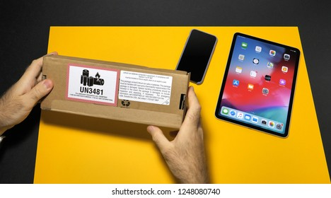 PARIS, FRANCE - NOV 16, 2018: Man unboxing latest box with Li-Ion bateries Apple Pencil 2 manufactured by Apple Computers in modern office environment yellow table