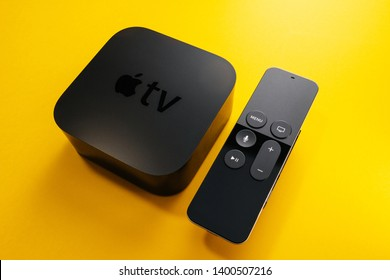 Paris, France - Nov 16, 2018: Side view of from above at new black Apple TV 4K media streaming by Apple Computers  against yellow background - tilt-shift lens used