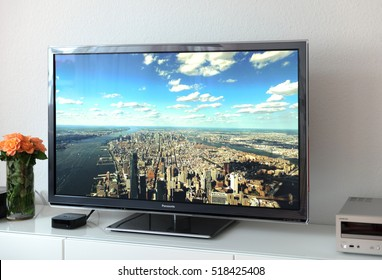 PARIS, FRANCE - NOV 21, 2015: Apple TV 4k device next to 4k Pansonic Plasma OLED display projecting the typical Apple Screensaver of aerial city