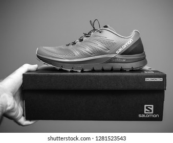 PARIS, FRANCE - NOV 22, 2018: Man holding against gray background a box with a pair of new Salomon Sense Pro Max everyday trail running performance with maximum cushioning black and white