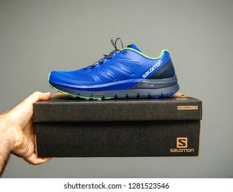 PARIS, FRANCE - NOV 22, 2018: Man holding against gray background a box with a pair of new bluew Salomon Sense Pro Max everyday trail running performance shoes with maximum cushioning.