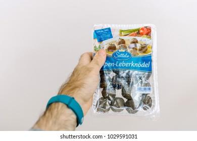 PARIS, FRANCE - NOV 25, 2017: Man hand holding against white background package of Meatballs Sopen-Leberknodel by Settele